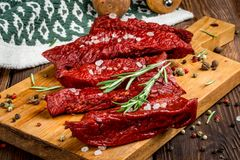 Smoked red deer maral filleted on a wooden background. Close-up Royalty Free Stock Images