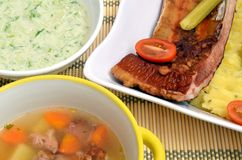 Smoked rib with potato, soap and cucumber salad. Smoked rib with mashed potato, soap and cucumber salad lunch Royalty Free Stock Photography
