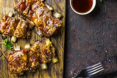 Smoked Roasted pork ribs over black background. Barbeque spicy ribs. Traditional american BBQ food. Dinner for a low-carb, keto diet royalty free stock image