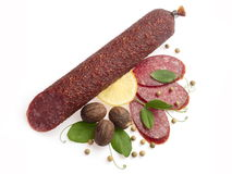 Smoked salami decorated with lemon, walnuts... Smoked salami decorated with lemon, walnuts, pepper and leafs of green pea over white background Stock Photography