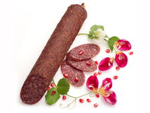 Smoked salami with flowers and pomegranate. Smoked salami decorated with flowers and pomegranate over white background Stock Images