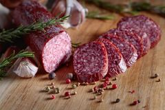 Smoked salami on a old wooden table. Sausages with rosemary , garlic and pepper royalty free stock image