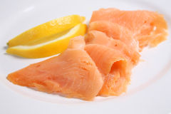 Smoked Salmon. Slices of smoked salmon with lemon slices on a white plate. Short DOF, focus on center of frame Stock Images