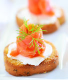 Smoked salmon appetizer. Smoked salmon or lox with cream cheese and dill on herb crostini Stock Photo