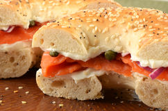 Smoked salmon on bagel. Smoked salmon or lox with cream cheese, red onion and capers on poppy seed and sesame seed bagel in horizontal format Stock Images