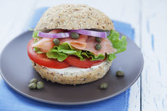 Smoked salmon burger. Delicious smoked salmon burger with lettuce, onions, tomato, capers and cream cheese Royalty Free Stock Photo