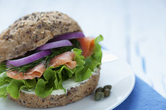 Smoked salmon burger. Delicious smoked salmon burger with lettuce, onions, dill and cream cheese Stock Photo