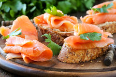 Smoked salmon canape. Delicious homemade smoked salmon canape garnished with a fresh parsley leaf stock image