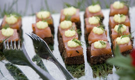 Smoked salmon canapes. Tastefull smoked salmon canapes with cream and dill on it in dish and serving tongs Stock Image