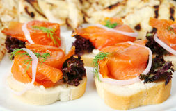 Smoked salmon canapes. A plate of smoked salmon canapes on french bread, garnished with lettuce, dill and an onion ring Royalty Free Stock Image
