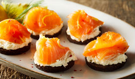 Smoked salmon canapes on quark. Or cream cheese seasoned with spices and served as an appetizer with cocktails, close up view on a plate Royalty Free Stock Images