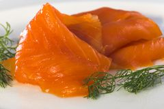 Smoked salmon with dill. There are some pieces of salmon with dill on a dish royalty free stock photos