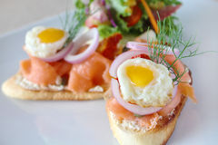Amuse bouche Smoked salmon and eggs on toasted bread Stock Image