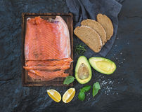Smoked salmon filet with lemon, avocado, fresh herbs and bred on wooden serving board over dark stone backdrop Stock Image