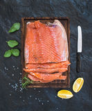 Smoked salmon filet with lemon, fresh herbs and bred on wooden serving board over dark stone backdrop Royalty Free Stock Photos