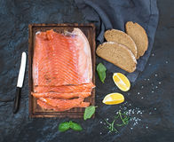 Smoked salmon filet with lemon, fresh herbs and bred on wooden serving board over dark stone backdrop Royalty Free Stock Photo