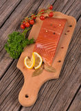 Smoked salmon fillet. With vegetables on the cutting board on the old wooden surface Stock Photos
