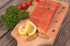 Smoked salmon fillet. With vegetables on the cutting board on the old wooden surface Stock Images