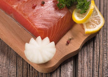 Smoked salmon fillet. With vegetables on the cutting board on the old wooden surface Royalty Free Stock Image