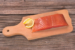 Smoked salmon fillet. With vegetables on the cutting board on the old wooden surface Royalty Free Stock Photo