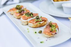 Smoked Salmon on Grilled Seven Grain Bread topping with prickled and sliced cucumber on the white plate at Dubai.  Stock Image