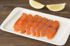 Smoked salmon with lemon on a white plate and wooden table. Smoked salmon with lemon on a white plate and a wooden table cut into thin slices Royalty Free Stock Photos