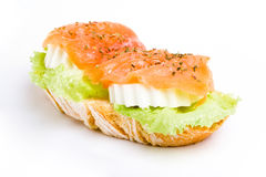 Smoked salmon, lettuce and cheese snack. Slice of french bread with lettuce and fresh cheese topped with sliced salmon. white background Royalty Free Stock Photos