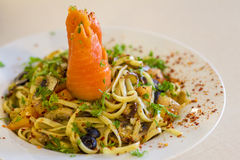 Smoked salmon linguine aglio olio. Linguine aglio olio smoked salmon with sundried tomatoes, olives, mixed herbs and chili flakes served on a white plate Royalty Free Stock Image