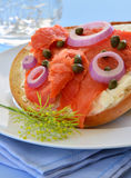 Smoked salmon lox on Asiago cheese bagel. Smoked salmon lox with cream cheese capers and red onion on toasted Asiago cheese bagel Royalty Free Stock Image