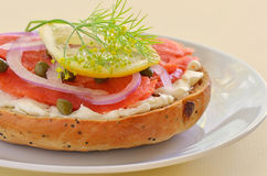 Smoked salmon lox on Asiago cheese bagel. Smoked salmon lox with cream cheese capers and red onion on toasted Asiago cheese bagel Stock Photo