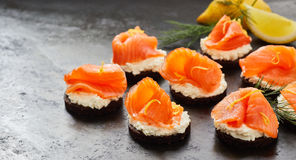 Smoked salmon or lox canapes panorama. Gourmet fresh smoked salmon or lox on quark cheese canapes in a panorama format for a header or banner with copy space Stock Image