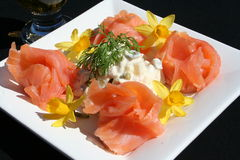 Smoked salmon with mixed salad. Salmon with salad on white plate with decoration of mini daffodils Stock Photography
