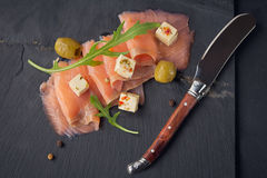 Smoked salmon, olives and arugula on dark plate. Salted fish Stock Photography