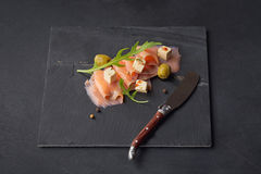 Smoked salmon, olives and arugula on dark plate. Salted fish Royalty Free Stock Photo