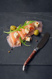 Smoked salmon, olives and arugula on dark plate. Salted fish Royalty Free Stock Photos