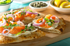 Smoked Salmon Pizza. A delicious home made smoked salmon pizza with cream cheese, red onion, capers and baby arugula Stock Photos