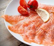 Smoked Salmon on plate. With cherry tomato and lemon Stock Image