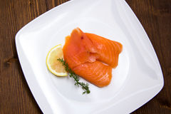 Smoked salmon on plate on wood from above Royalty Free Stock Image