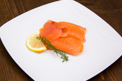 Smoked salmon on plate on wood Royalty Free Stock Image