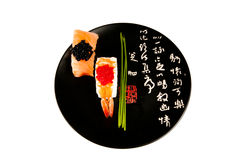 Smoked salmon and prawn sushi, Japanese plate. Smoked salmon and prawn nigiri sushi garnished with chives on a balck plate with Japanese writing in white and Royalty Free Stock Photos