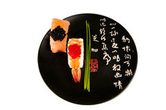 Smoked salmon and prawn sushi, Japanese plate. Smoked salmon and prawn nigiri sushi garnished with chives and red and black fish eggs on a black plate with Stock Photography