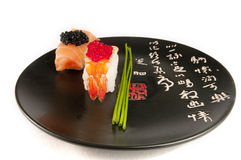 Smoked salmon and prawn sushi, Japanese plate. Smoked salmon and prawn nigiri sushi garnished with chives and red and black fish eggs on a black plate with Royalty Free Stock Images