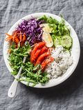 Smoked salmon, rice, vegetables buddha power bowl on gray background, top view. Red cabbage, carrots, arugula, rice, smoked salmon