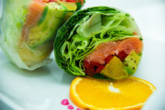 Smoked Salmon Roll with mandarine on the platea. Sliced, crunchy carrots, red cabbage, celery and cucumber with rucola, red and yellow capsicum with lime and Stock Photos
