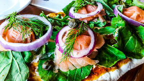 Smoked Salmon Salad with onions and greens on cream cheese and crispy bread. Stock Photography