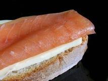 Smoked salmon sandwich. Salmon sandwich on black reflective surface stock photography