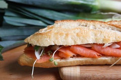 Smoked salmon sandwich on cutting board Stock Image