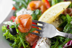 Smoked salmon slice and olive on fork closeup Stock Photos