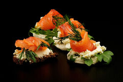 Smoked salmon snacks. Appetizers Smoked salmon with dill on cracker isolated on black background Royalty Free Stock Photo