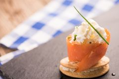 Smoked Salmon and soft chees canapes appetizers. On a black plate Stock Photos